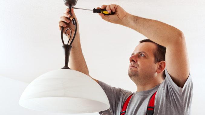 Elektriker schließt eine Lampe an